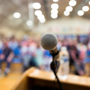 microphone at podium with blurred people in an auditorium
